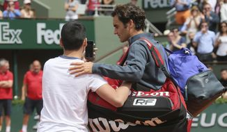 A boy who climbed down from the stands takes a selfie with Switzerland's Roger Federer in the first round match of the French Open tennis tournament against Colombia's Alejandro Falla at the Roland Garros stadium, in Paris, France, Sunday, May 24, 2015. (AP Photo/David Vincent)
