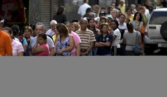 Shoppers queue outside of a supermarket in downtown Caracas, Venezuela, in this Jan. 8, 2015, file photo. (AP Photo/Fernando Llano, File)