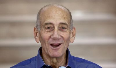 Former Israeli Prime Minister Ehud Olmert speaks to the media after hearing the verdict in his trial, in Jerusalem's District Court in this July 10, 2012, file photo. Olmert has been sentenced to eight months in prison for unlawfully accepting money from a U.S. supporter. The Monday, May 25, 2015, verdict in Jerusalem District Court caps a dramatic downfall of a man who only years earlier led the country and hoped to bring about a historic peace agreement with the Palestinians. (AP Photo/Ariel Schalit, File)