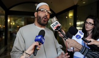 In this April 18, 2011, file photo, Man Haron Monis speaks to the media as he leaves the Downing Centre in Sydney after a pre-trial hearing where he is accused of sending offending letters to the families of soldiers killed in Afghanistan. The man who took 18 people hostage at a Sydney cafe last year was educated and erratic, secretive about his own life, lawyers told an inquest Monday, May 25, 2015. (Dean Lewins/AAP Image via AP, File)