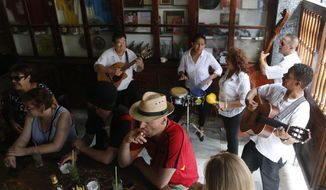 In this Sunday, May 24, 2015, photo, tourists enjoy cigars, mojitos and live music at the Bodeguita del Medio Bar, frequented by the late American novelist Ernest Hemingway in Old Havana, Cuba. The thaw in relations between the U.S. and Cuba has led to a dramatic 36 percent increase in visits by Americans to Cuba since January compared to the same period last year, along with a 14 percent rise in arrivals from around the world. (AP Photo/Desmond Boylan)