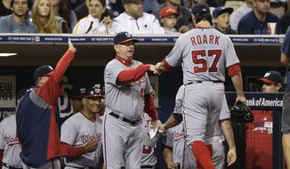 Washington Nationals starting pitcher Tanner Roark (57) is greeted at the dugout by defensive coordinator and advance coach Mark Weidemaier after getting the last out against the San Diego Padres during the eighth inning of a baseball game Friday, June 6, 2014, in San Diego. (AP Photo/Gregory Bull)
