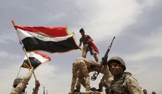 Iraqi army soldiers celebrate during a training mission outside Baghdad, Iraq, Wednesday, May 27, 2015. Islamic State extremists unleashed a wave of suicide attacks targeting the Iraqi army in western Anbar province, killing at least 17 troops in a major blow to government efforts to dislodge the militants from the sprawling Sunni heartland, an Iraqi military spokesman said Wednesday. (AP Photo/Khalid Mohammed)