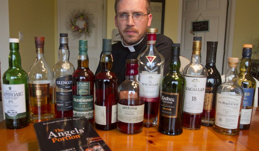 """The Rev. Christopher Thoma has written a book on whisky, particularly Scotch whisky, having become a passionate whisky 'enjoyer', Friday, May 8, 2015. Bottles from his whisky cupboard represent the major Scotch whisky regions of Scotland, and his book is entitled """"The Angels' Portion: A Clergyman's Whisky Narrative."""" (Gillis Benedict/Livingston Daily Press & Argus via AP)"""
