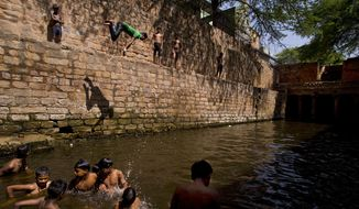 A young boy dives into a water tank on a hot summer day in New Delhi, India, Wednesday, May 27, 2015. Delhi recorded a maximum temperature of 42 degrees Celsius on Wednesday. In southern India, hundreds of people have died since the middle of April as soaring summer temperatures scorch the country, officials said Tuesday. (AP Photo/Saurabh Das)