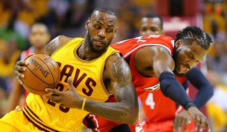 Cleveland Cavaliers LeBron James, left, and Hawks DeMarre Carroll battle for a loose ball during game four of the Eastern Conference Finals on Tuesday, May 26, 2015, in Cleveland.      (Curtis Compton/Atlanta Journal-Constitution via AP)  MARIETTA DAILY OUT; GWINNETT DAILY POST OUT; LOCAL TELEVISION OUT; WXIA-TV OUT; WGCL-TV OUT