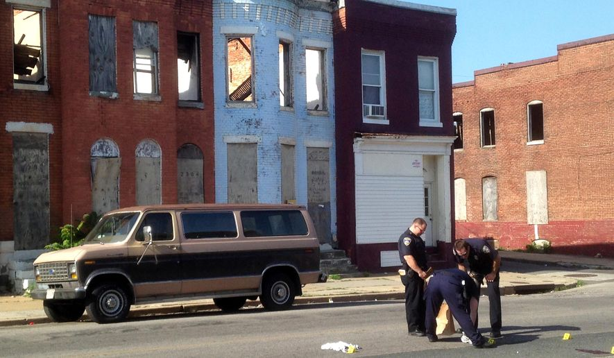 Police pick up a pair of shoes after a double shooting in Baltimore in this May 24, 2015, file photo. (Colin Campbell/The Baltimore Sun via AP, File)