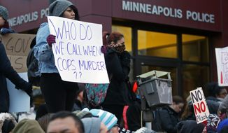 Demonstrators rally outside outside the Minneapolis Police Department's Third Precinct to protest police brutality on Nov. 25, 2014, in Minneapolis, following the previous day's announcement that a grand jury has decided not to indict Ferguson, Mo., police officer Darren Wilson in the shooting death of unarmed, black 18-year-old Michael Brown. (Associated Press) **FILE**