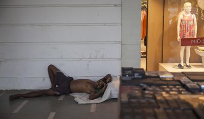 An Indian homeless man sleeps on a pavement in a market area on a hot summer day in New Delhi, India, Wednesday, May 27, 2015. In southern India, hundreds of people have died since the middle of April as soaring summer temperatures scorch the country, officials said Tuesday. (AP Photo/Tsering Topgyal)