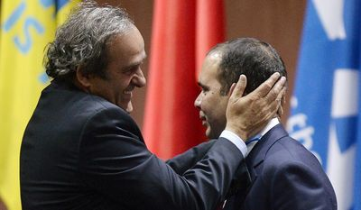 Prince Ali bin al-Hussein, right, with UEFA President Michel Platini, left, after announcing his withdrawal during the 65th FIFA Congress at the Hallenstadion in Zurich, Switzerland, Friday, May 29, 2015. Sepp Blatter has been re-elected as FIFA president for a fifth term, chosen to lead world soccer despite separate U.S. and Swiss criminal investigations into corruption. The 209 FIFA member federations gave the 79-year-old Blatter another four-year term on Friday after Prince Ali bin al-Hussein of Jordan conceded defeat after losing 133-73 in the first round. (Walter Bieri/Keystone via AP)