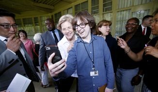 Senator Elizabeth Warren meets with members of the Berkshire Brigades and takes a selfie with BCC student Jacob Robbins before delivering the commencement address at the Berkshire Community College graduation ceremony at Tanglewood in Lenox, Mass,  Friday, May 29, 2015. (AP Photo/Stephanie Zollshan/The Berkshire Eagle via AP)