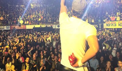 """In this photo provided by Francis Ramsden, Enrique Iglesias performs while holding his bloodied and bandaged right hand behind his back during a concert in Tijuana, Mexico on Saturday, May 30, 2015. A representative for the singer says in a statement to The Associated Press that Iglesias was """"semi-treated"""" offstage after his fingers were sliced when he grabbed a drone during the concert. (Francis Ramsden via AP)"""