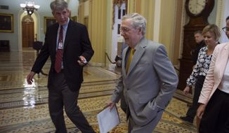 Senate Majority Leader Mitch McConnell walks to the Senate Chamber to begin a special session to extend surveillance programs Sunday. (AP Photo)