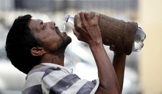 An Indian drinks water from a bottle on a hot summer day in Allahabad, India, on May 31, 2015. Heat-related conditions, including dehydration and heat stroke, have killed more than 2,000 people since mid-April in the southern Indian states of Andhra Pradesh and Telangana, according to state officials. (Associated Press) **FILE**