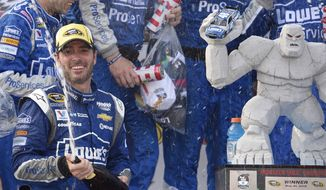 Jimmie Johnson sprays sparking wine as he celebrates in Victory Lane after he won the NASCAR Sprint Cup series auto race, Sunday, May 31, 2015, at Dover International Speedway in Dover, Del. (AP Photo/Nick Wass)