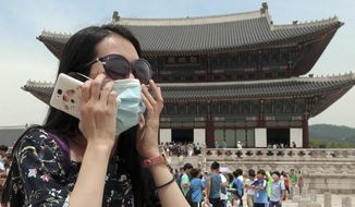 An unidentified Chinese tourist wearing a mask by way of precaution against the Middle East Respiratory Syndrome virus visits Gyeongbok Palace in Seoul, South Korea Monday, June 1, 2015. Authorities say more than 680 people in South Korea are placed in isolation after having contacts with those infected with a virus that has killed hundreds of people in the Middle East. (Choi Jae-koo/Yonhap via AP) KOREA OUT