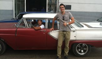 This May 15, 2015 photo shows Mario Otero in front of a classic American car driven by his friend Camilo Rodriguez in Havana, Cuba. Otero, 25, works as a waiter in one of Havana's best restaurants, has a tourism degree, moonlights as a private tour guide with a goal of someday opening his own tourism agency, and sees increased tourism in Cuba as a key to achieving his dreams. Otero, who speaks English and French, is also renovating a house he hopes to rent to tourists. (AP Photo/Beth J. Harpaz)