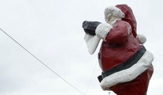 This April 24, 2006 file photo a school bus drives down Saint Nicholas Drive in front of a Santa Claus statue at the Santa Claus House gift shop in North Pole, Alaska. (John Hagen/The Fairbanks Daily News-Miner via AP, File) MANDATORY CREDIT