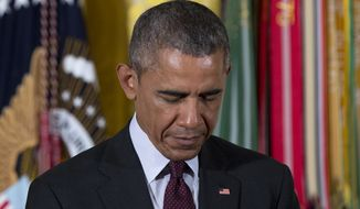 President Barack Obama bows his head in prayer in the East Room of the White House in Washington, Tuesday, June 2, 2015, before posthumously bestowing the Medal Of Honor on Army Sgt. William Shemin and Army Pvt. Henry Johnson during a ceremony. Two World War I Army heroes, one black, one Jewish, are finally getting the Medal of Honor they may have been denied because of discrimination, nearly 100 years after bravely rescuing comrades on the battlefields of France. (AP Photo/Carolyn Kaster)