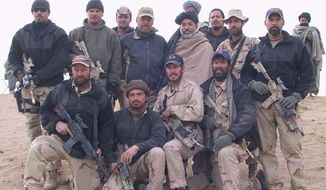 A photo of Army Lt. Col. Jason Amerine and his team with Afghan freedom fighters in 2001. Col. Amerine is in the first row, second from the right. The turbaned man standing in the second row is Hamid Karzai, who later became Afghanistan's first democratically elected president.