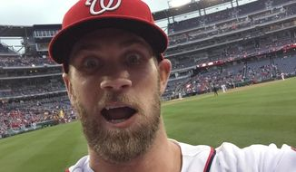 Washington Nationals outfielder Bryce Harper takes a photo of himself with a cell phone tossed to him by fan Jamie Roach, Tuesday, June 2, 2015, at Nationals Park in Washington. Roach noticed Harper gesturing for her picture-taking cell phone before the second game of the Nationals' doubleheader against the Toronto Blue Jays. Roach tossed the phone and Harper made the catch. Then he made Roach's day and then some by snapping a wide-eyed, silly face picture of himself. (Bryce Harper via AP)