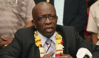 In this June 2, 2011, file photo, suspended FIFA executive Jack Warner gestures during a news conference at the airport in Port-of-Spain, Trinidad and Tobago. Interpol added six men with ties to FIFA to its most wanted list on Wednesday, June 3, 2015, issuing an international alert for two former FIFA officials and four executives on charges including racketeering and corruption. Two of the men, former FIFA vice president Jack Warner of Trinidad and former executive committee member Nicolas Leoz of Paraguay, have been arrested in their home counties. Warner has since been released and Leoz is under house arrest.  (AP Photo/Shirley Bahadur, File)