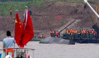 Rescuers work on the capsized ship, center, on the Yangtze River in China's Hubei province, Wednesday, June 3, 2015. The capsizing late Monday of the Eastern Star in the Yangtze River in southern China is on track to become the country's deadliest maritime disaster in seven decades. (AP Photo/Andy Wong)