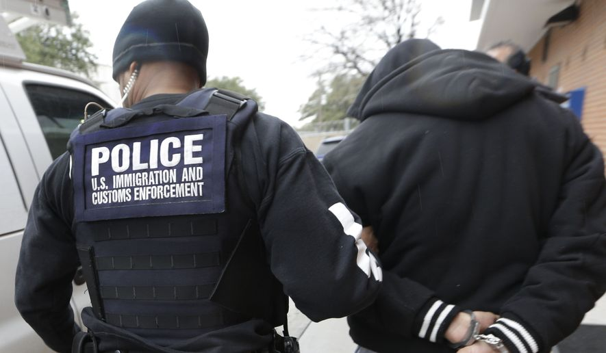 A U.S. Immigration and Customs Enforcement agent escorts a handcuffed illegal immigrant convicted of a felony that was taken into custody during an early morning operation in Dallas on March 6, 2015. (Associated Press) ** FILE **