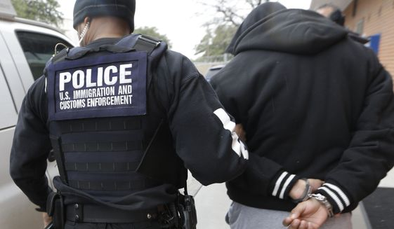 A U.S. Immigration and Customs Enforcement agent escorts a handcuffed illegal immigrant convicted of a felony that was taken into custody during an early morning operation in Dallas on March 6. (Associated Press)
