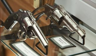 The first actual department issued Merwin Hulbert handgun, right, for the Detroit Police Department in 1880 sits on display next to the second generation of issued firearm  Smith and Wesson safety hammerless handgun from 1895-1905 at the new Detroit Police Museum and Gift Shop on Tuesday May 12, 2015 located in the Detroit Public Safety Headquarters in Detroit. (Ryan Garza/Detroit Free Press via AP)  DETROIT NEWS OUT; TV OUT; MAGS OUT; NO SALES; MANDATORY CREDIT DETROIT FREE PRESS