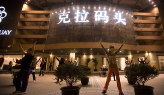 In this April 13, 2015, photo, women dance to music in a plaza outside of an upscale European import furniture store in Wenzhou city in eastern China's Zhejiang Province. As Italy's economy was heading off a cliff, police couldn't help but notice that the country's Chinese communities were booming. (AP Photo/Mark Schiefelbein)