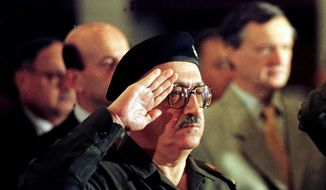 In this Dec. 2, 1998, file photo, former Iraqi foreign minister Tariq Aziz stands to attention as the Iraqi national anthem is played at a conference in Baghdad, Iraq. Officials say Aziz has died in a hospital in southern Iraq on Friday, June 5, 2015. (AP Photo/Peter Dejong, File)