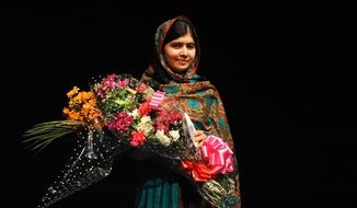 In this Friday, Oct. 10, 2014, file photo, Malala Yousafzai poses with a bouquet after speaking during a media conference at the Library of Birmingham, in Birmingham, England, after she was named as winner of The Nobel Peace Prize. (AP Photo/Rui Vieira, File)