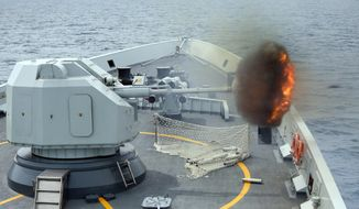 """An anti-surface gunnery is fired from China's Navy missile frigate Yulin during the """"Exercise Maritime Cooperation"""" by Singapore and Chinese navies in the South China Sea, May 24, 2015. (Bao Xuelin/Xinua via AP, File) ** FILE **"""