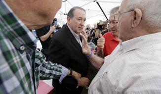 Republican presidential candidate, former Arkansas Gov. Mike Huckabee, center, speaks to supporters during a fundraiser for U.S. Sen. Joni Ernst, R-Iowa, Saturday, June 6, 2015, in Boone, Iowa. (AP Photo/Charlie Neibergall)