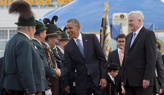US President Barack Obama, joined by Horst Seehofer, Minister President of Bavaria, right, is greeted by traditionally dressed Bavarian men and women as he arrives on Air Force One at the airport in Munich, southern Germany, Sunday, June 7, 2015, en route to the G-7 summit at the Schloss Elmau hotel near Garmisch-Partenkirchen, southern Germany.   (AP Photo/Carolyn Kaster)