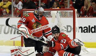 Chicago Blackhawks' Trevor van Riemsdyk, right, slides past goalie Corey Crawford while chasing after a loose puck during the third period in Game 3 of the NHL hockey Stanley Cup Final against the Tampa Bay Lightning on Monday, June 8, 2015, in Chicago. (AP Photo/Nam Y. Huh)