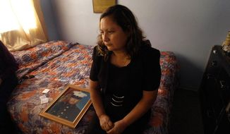 This Nov. 19, 2004, file photo shows Rosa Maria Peralta sitting on her son's bed in his bedroom ash she reflects back on her memories with her son, Marine Sgt. Rafael Peralta, in San Diego, Calif.   (Nelvin Cepeda/U-T San Diego via AP, File)
