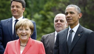 German Chancellor Angela Merkel (front left) poses with (from left) Italian Prime Minister Matteo Renzi, Iraqi Prime Minister Haider al-Abadi and U.S. President Barack Obama during a group photo of G-7 leaders and Outreach guests at the G-7 summit at Schloss Elmau hotel near Garmisch-Partenkirchen on June 8, 2015. (Associated Press) **FILE**