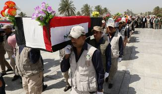 In this picture taken Monday, June 8, 2015, mourners carry the flag-draped coffins at the Shaheed or Martyrs monument, during a symbolic funeral for Iraqi soldiers killed by Islamic State group militants when they overran Camp Speicher military base in June 2014, in Baghdad, Iraq. (AP Photo/ Hadi Mizban)