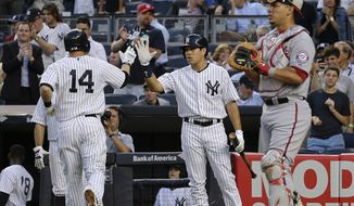 New York Yankees' Stephen Drew (14) is greeted by Ramon Flores as Washington Nationals catcher Wilson Ramos waits after Drew hit a solo home run during the third inning of a baseball game, Tuesday, June 9, 2015, in New York. (AP Photo/Julie Jacobson)