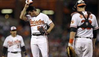 Baltimore Orioles starting pitcher Miguel Gonzalez, center, wipes sweat from his face while teammates Ryan Flaherty, back left, and Matt Wieters approach as he is relieved in the fifth inning of a baseball game against the Boston Red Sox, Tuesday, June 9, 2015, in Baltimore. Baltimore won 1-0. (AP Photo/Patrick Semansky)
