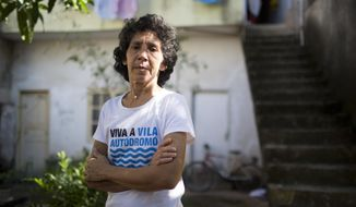Maria da Penha, 50, poses for a photo at the entrance of her house at Vila Autodromo favela, near the Olympic Park in Rio de Janeiro, Brazil, Tuesday, June 9, 2015. Pehna's nose was broken and her left eye was blackened last week when she was pushed to the ground as residents clashed with guards trying to carry out an eviction. Pehna lives just 100 meters from the Olympic Park construction. (AP Photo/Mauro Pimentel)