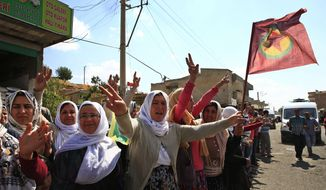 Kurdish women, one waving a flag of the outlawed Kurdish rebel group, the PKK, right, flash the V-sign and applaud while lining the road, as the convoy carrying the body of Hanim Dabaan, killed in fighting with the militants of the Islamic State group in Kobani, Syria, is driven by through Suruc, on the Turkey-Syria border, Thursday, June 11, 2015. Keith Broomfield, 20 from Massachusetts, died June 3 in battle in a Syrian village near Kobani, making him likely the first U.S. citizen to die fighting alongside  Kurds against the Islamic State group. (AP Photo/Lefteris Pitarakis)