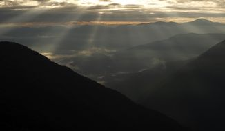 Shafts of sunlight filter though clouds onto the mountains in Coroico, Bolivia, Wednesday, June 10, 2015, where nuns of the Order of Saint Clare amass hostias in preparation for the July visit of Pope Francis. (AP Photo/Juan Karita)