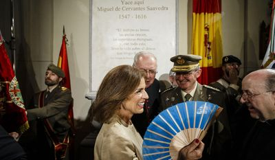 Madrid Mayor Ana Botella, center, uses a fan as she smiles and talks with authorities after a ceremony unveiling a funeral monument holding bone remains believed to include those of Spanish writer Miguel de Cervantes in a Madrid convent, Spain, Thursday, June 11, 2015. (AP Photo/Daniel Ochoa de Olza)