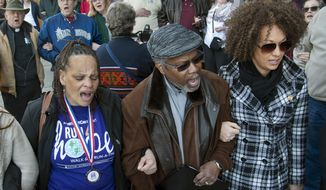"In this Friday, March 6, 2015, file photo, from left, Della Montgomery-Riggins, Charles Thornton and Spokane NAACP president Rachel Dolezal link arms and sing ""We Shall Overcome"" at a rally in downtown Spokane, Wash., responding to a racist and threatening package received by Dolezal. Dolezal is now facing questions about whether she lied about her racial identity, with her family saying she is white but has portrayed herself as black. (Dan Pelle/The Spokesman-Review via AP, File)"