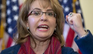 "FILE - In this March 4, 2015, file photo, former U.S. Rep. Gabrielle ""Gabby"" Giffords of Arizona gestures as she speaks on Capitol Hill in Washington. Giffords is being recognized with a Navy ship named in her honor at a shipyard in Mobile, Alabama. Giffords is set to attend the Saturday, June 13, 2015,  christening of the USS Gabrielle Giffords.  (AP Photo/Carolyn Kaster, File)"