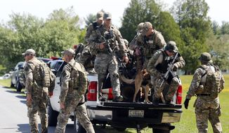 Law enforcement officers get off a truck as they return to their vehicles after searching a wooded area on Sunday, June 14, 2015, in Schuyler Falls, N.Y. Law enforcement personnel are in the ninth day of searching for David Sweat and Richard Matt, two killers who used power tools to cut their way out of Clinton Correctional Facility in Dannemora in northern New York. (AP Photo/Mike Groll)