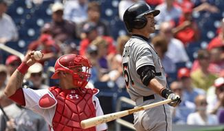 Miami Marlins left fielder Ichiro Suzuki (51) in between pitches with Washington Nationals catcher Wilson Ramos (40) during the fourth inning of their baseball game at Nationals Park in Washington, Wednesday, May 6, 2015. (AP Photo/Susan Walsh)